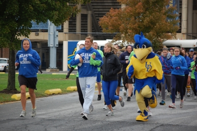 YoUDee leads Blue Hen student-athletes from Delaware Stadium on their way to Towson University.