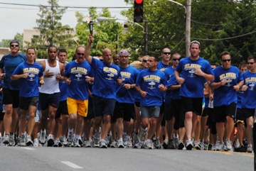 Law enforcement officers run through the streets of Wilmington as part of the annual 160-mile Torch Run leading up to Summer Games.